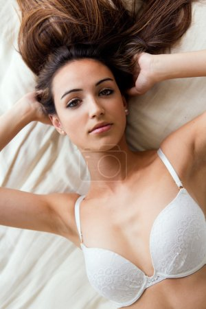 Photo for Portrait of beautiful girl with perfect body lying on the bed. Isolated on white. - Royalty Free Image
