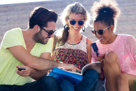 Photo for Portrait of students group looking at a book in the street. - Royalty Free Image