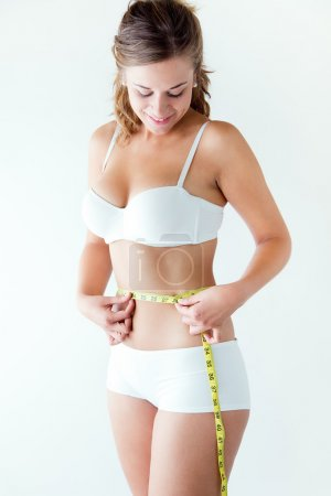 Young woman measuring her waist by measure tape.
