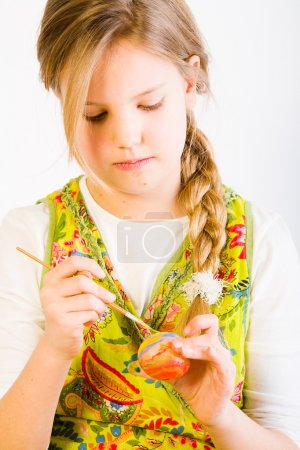 Young girl painting an egg