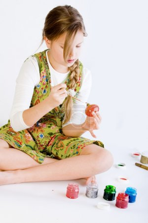 Young girl painting her easter eggs