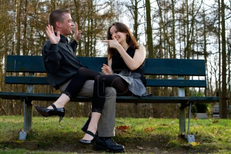 Photo for Man and girlfriend on a bench in a park having fun - Royalty Free Image
