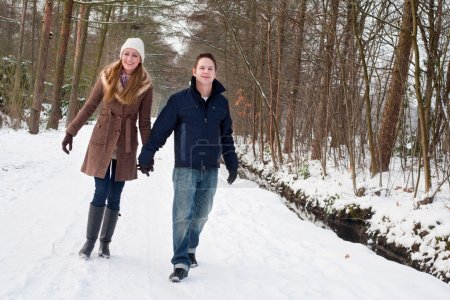 Young couple have a forest winter walk