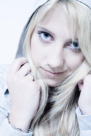 Studio portrait of friendly looking a long blond girl