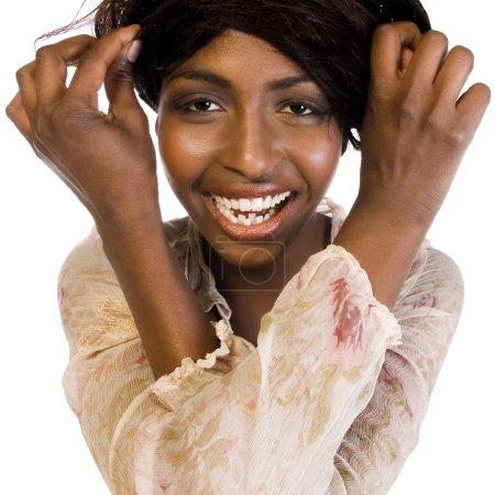 Photo pour Un portrait de beauté tiré d'un mannequin africain en studio qui trompe avec ses cheveux - image libre de droit