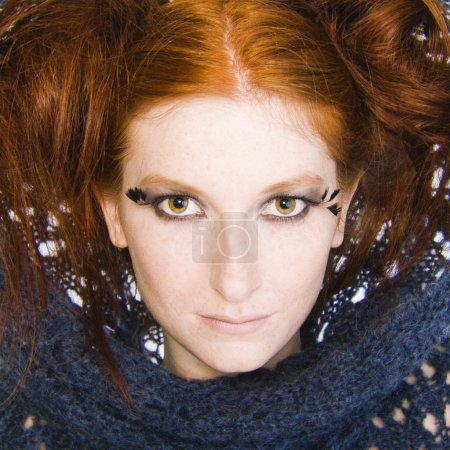 Studio portrait of a natural redhead with a blue s...