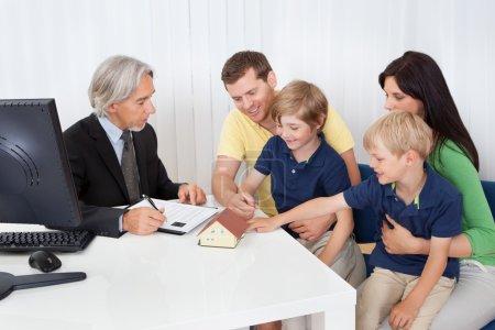 Photo pour Famille dans le planificateur de construction parler-Agence immobilière - image libre de droit