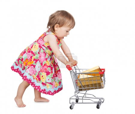Photo for Cute little barefoot girl in a colourful dress pushing a miniature wire shopping trolley isolated on white - Royalty Free Image