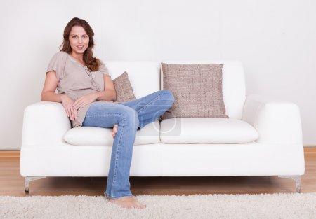 Foto de Casual mujer descalza en jeans sentado en un sofá de su sala de estar con una sonrisa alegre - Imagen libre de derechos