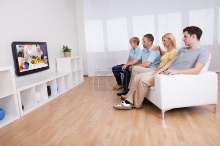 Photo pour Famille avec des adolescents assis ensemble sur un canapé dans le salon en regardant la télévision à écran large - image libre de droit