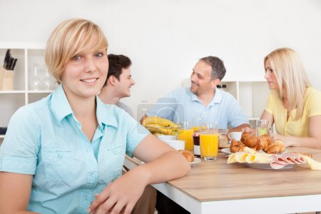 Teenage girl and family at breakfast