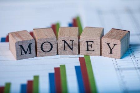 Photo pour Blocs en bois avec le lettrage Money sur le dessus des graphiques à barres ascendantes analysant la statique et la performance des actions sur le marché - image libre de droit
