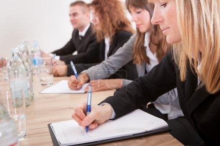 Foto de Jóvenes empresarias tomando nota en reunión con colegas - Imagen libre de derechos