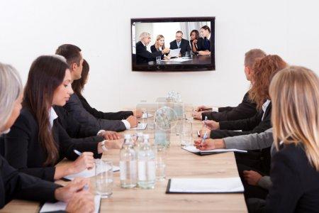 Foto de Empresarios sentado en la mesa de conferencias mirando la pantalla plana - Imagen libre de derechos