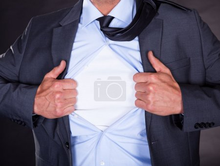 Photo pour Superhéros arrachant sa chemise sur fond noir - image libre de droit