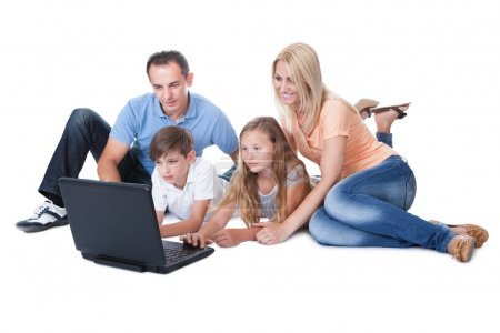 Foto de Una familia feliz con dos niños usando laptop aislado sobre fondo blanco - Imagen libre de derechos