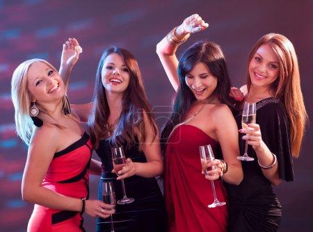 Photo pour Groupe de quatre femmes élégantes, debout dans une rangée de grillage avec flûtes de champagne - image libre de droit