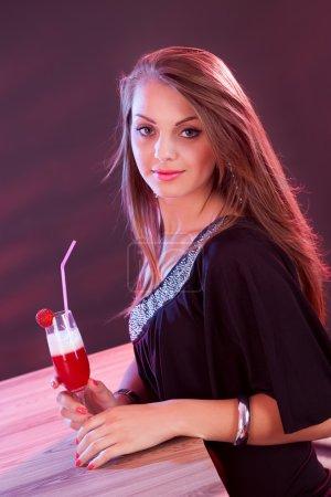 Photo pour Glamour belle femme dans une robe de soirée tenant un cocktail dans sa main tout en se tenant au bar dans une boîte de nuit - image libre de droit
