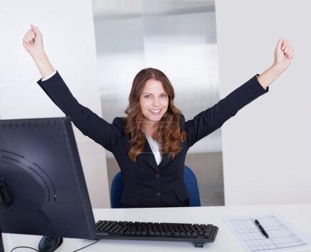 Photo pour Femme d'affaires jubilatoire lève les bras au-dessus de sa tête pour célébrer son succès assis dans son bureau - image libre de droit