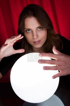 Photo pour Belle jeune diseuse de bonne aventure tenant ses mains autour d'une boule lumineuse alors qu'elle prédit l'avenir et ce qu'il contient - image libre de droit