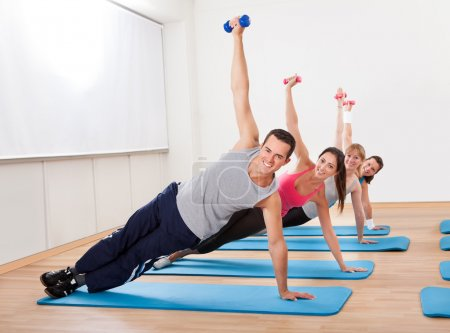 Photo for Large group of working out in a gym balanced on one hand on their mats while raising their other arm with a dumbbell - Royalty Free Image