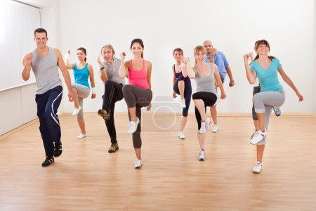 Photo for Large diverse group of doing aerobics exercises in a class in a gym in a health and fitness concept - Royalty Free Image