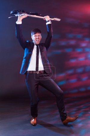 Photo pour Musicien masculin se produisant dans une boîte de nuit tenant sa guitare au-dessus de sa tête dans la jubilation dans le cadre de son acte - image libre de droit