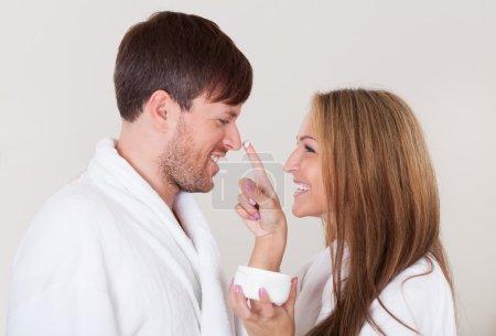 Photo pour Affectueux jeune couple rire comme la femme tout en s'amusant par les touches font face crème sur la fin du mans nez isolé sur blanc - image libre de droit