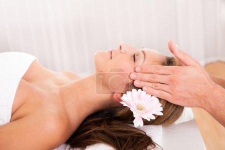 Photo pour Belle femme avec une fleur dans les cheveux profitant d'un soin spa souriant tandis qu'une esthéticienne masse doucement ses tempes - image libre de droit