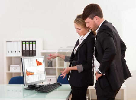 Two professional young business colleagues stand i...