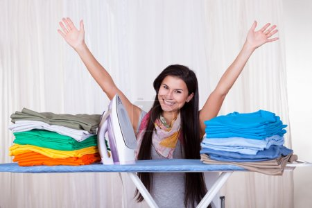 Photo for Happy woman throws her arms in the air because she has finished and folded all of the ironing - Royalty Free Image