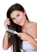 Smiling woman brushing long brunette hair