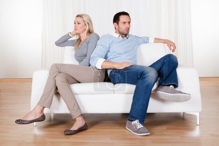 Photo for Couple who have fallen out over a disagreement sitting on a sofa - Royalty Free Image