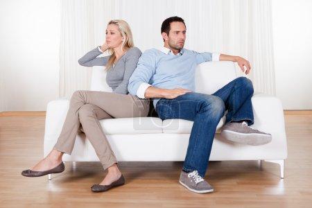Photo pour Couple qui ont tombé sur un désaccord assis sur un canapé - image libre de droit