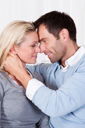 Photo pour Charmant couple ludique assis ensemble à la maison - image libre de droit
