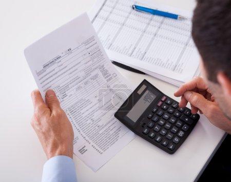 Photo pour Par-dessus l'épaule d'un homme vérifiant une facture sur une calculatrice - image libre de droit