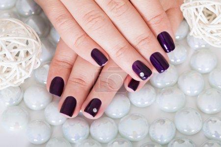 Photo pour Vue d'une femme affichant ses ongles manucurés belles à la mode avec vernis à ongles violet et un strass sur deux doigts de rognée - image libre de droit