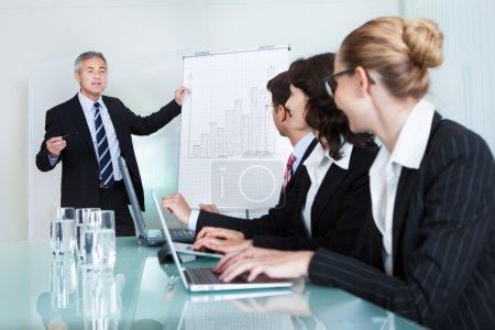 Photo pour Un dirigeant de dirigeants d'entreprises offrant une présentation à ses collègues au cours d'une réunion ou une formation commerciale interne - image libre de droit