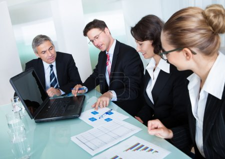 Photo for Group of diverse business executives holding a meeting around a table discussing graphs showing statistical analysis - Royalty Free Image