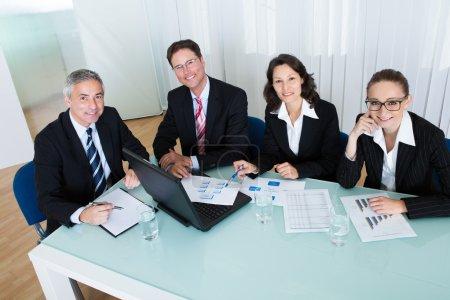 Photo pour Vue aérienne d'un groupe de dirigeants d'entreprise divers qui tiennent une réunion autour d'une table pour discuter de graphiques montrant l'analyse statistique - image libre de droit