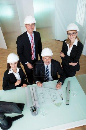Photo pour Vue aérienne d'un groupe d'architectes ou d'ingénieurs discuter un plan posé sur la table en face d'eux - image libre de droit