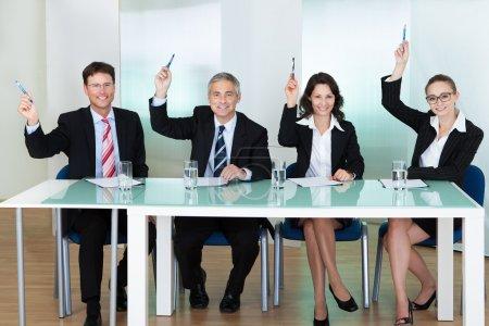 Photo pour Groupe d'agents de recrutement corporatif interviewant pour un poste vacant professionnel soulevant leurs stylos - image libre de droit