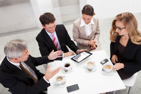 Photo pour Des collègues profitent d'une pause café souriant à quelque chose sur l'écran d'une tablette tenue par l'un des hommes - image libre de droit