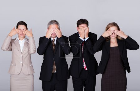 Four businesspeople holding their eyes shut