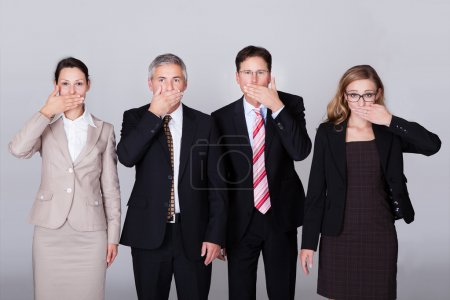 Photo for Four diverse businesspeople standing in a row gesturing for silence in a conceptual representation of the saying - Speak no evil - Royalty Free Image