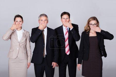 Photo pour Quatre hommes d'affaires divers debout dans une rangée de gestes pour le silence dans une représentation conceptuelle de la parole - Ne dites pas de mal - image libre de droit