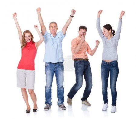 Foto de Dos parejas felices atractivas en ropa casual y pantalones vaqueros celebrar alzando sus brazos en el aire y gritando en blanco - Imagen libre de derechos
