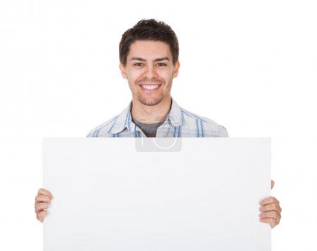 Photo pour Souriant beau jeune homme décontracté tenant un panneau blanc vierge devant sa poitrine avec copyspace pour votre texte - image libre de droit