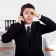 Worried stock broker talking on the phone backed b...