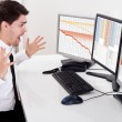 Worried stock broker looking at stock charts going...